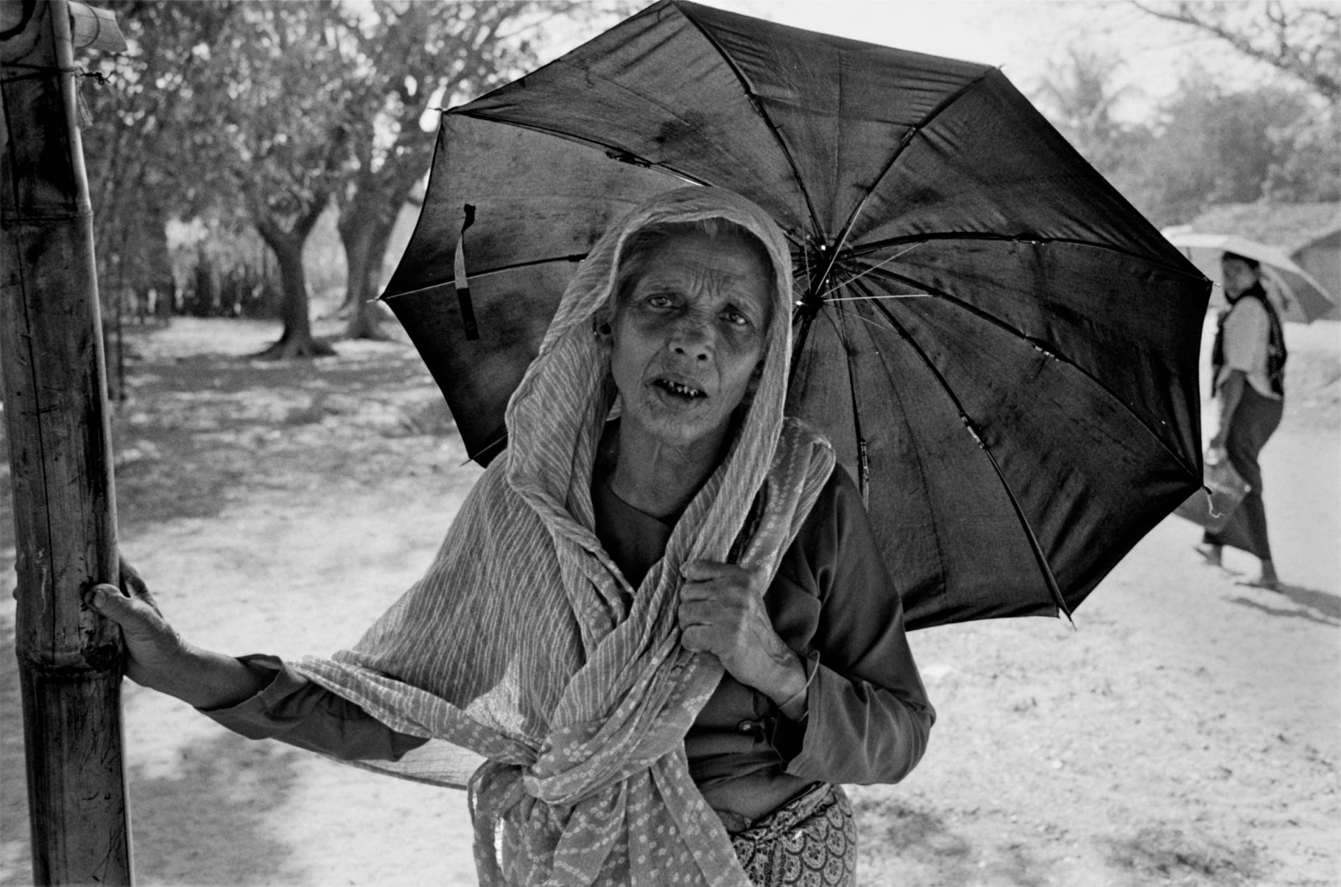 A Rohingya woman waits in the hot sun outside of a closed Da Paing medical clinic.  There is one health clinic to service more than 140,000 people living in more than a dozen IDP camps.  Sittwe, 2013.