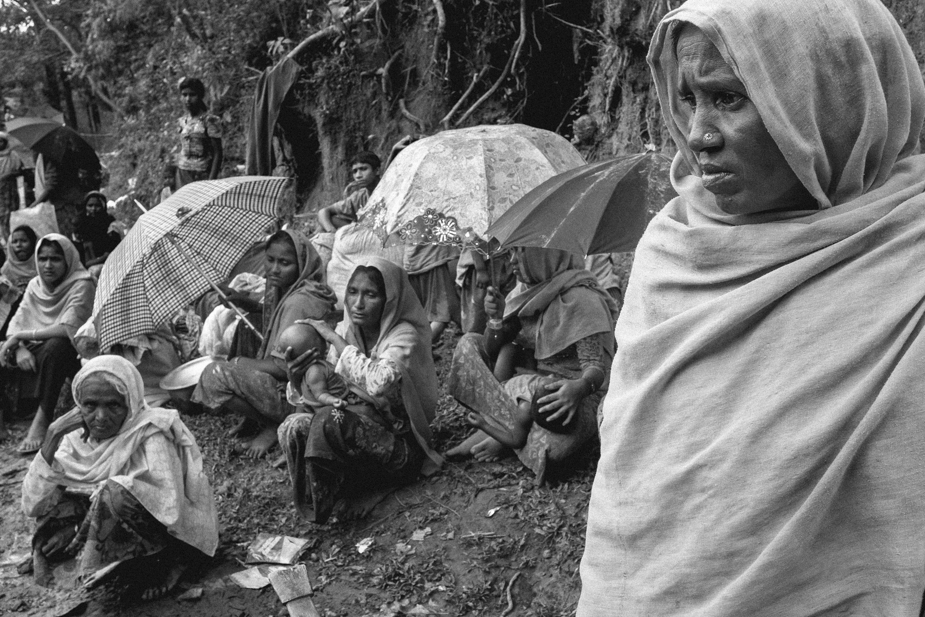 Rohingya women and children who just arrived in Bangladesh sit along the side of the road near Thaing Khali, Bangladesh.  All over the Cox's Bazar region of Bangladesh tens of thousands of Rohingya refugees from Myanmar line the sides of roads as they don't have the money to build a shelter in one of the sprawling makeshift camps.