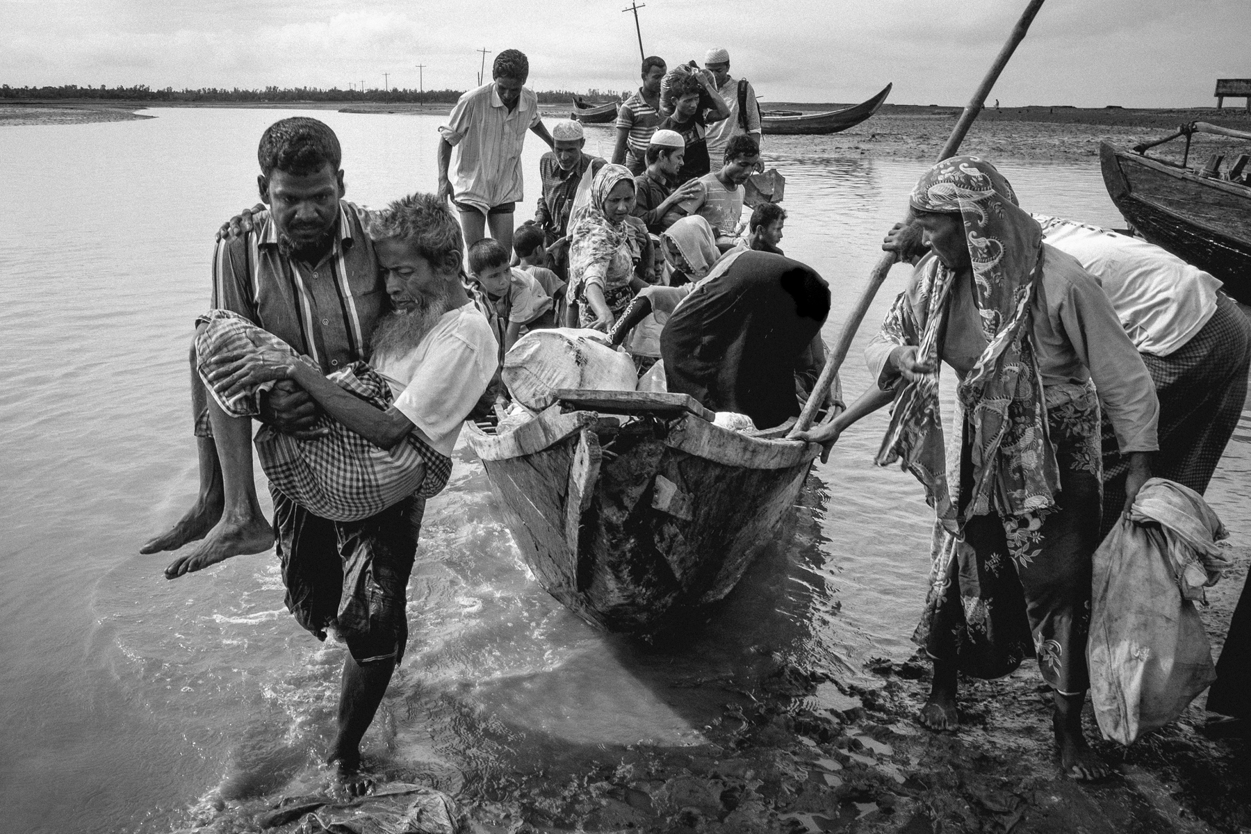A Bangladeshi boat driver carries a sickened 80 year old Halu to shore after ferrying a boat of Rohingya refugees from Atilla Para and Indin Para, Maungdaw to Bangladesh's mainland at Shah Parir Dwip.