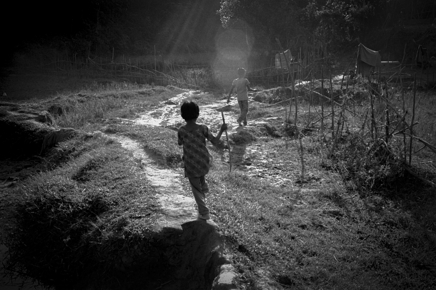 A Rohingya girl and boy run through the Himchari hills in Cox's Bazar, Bangladesh.