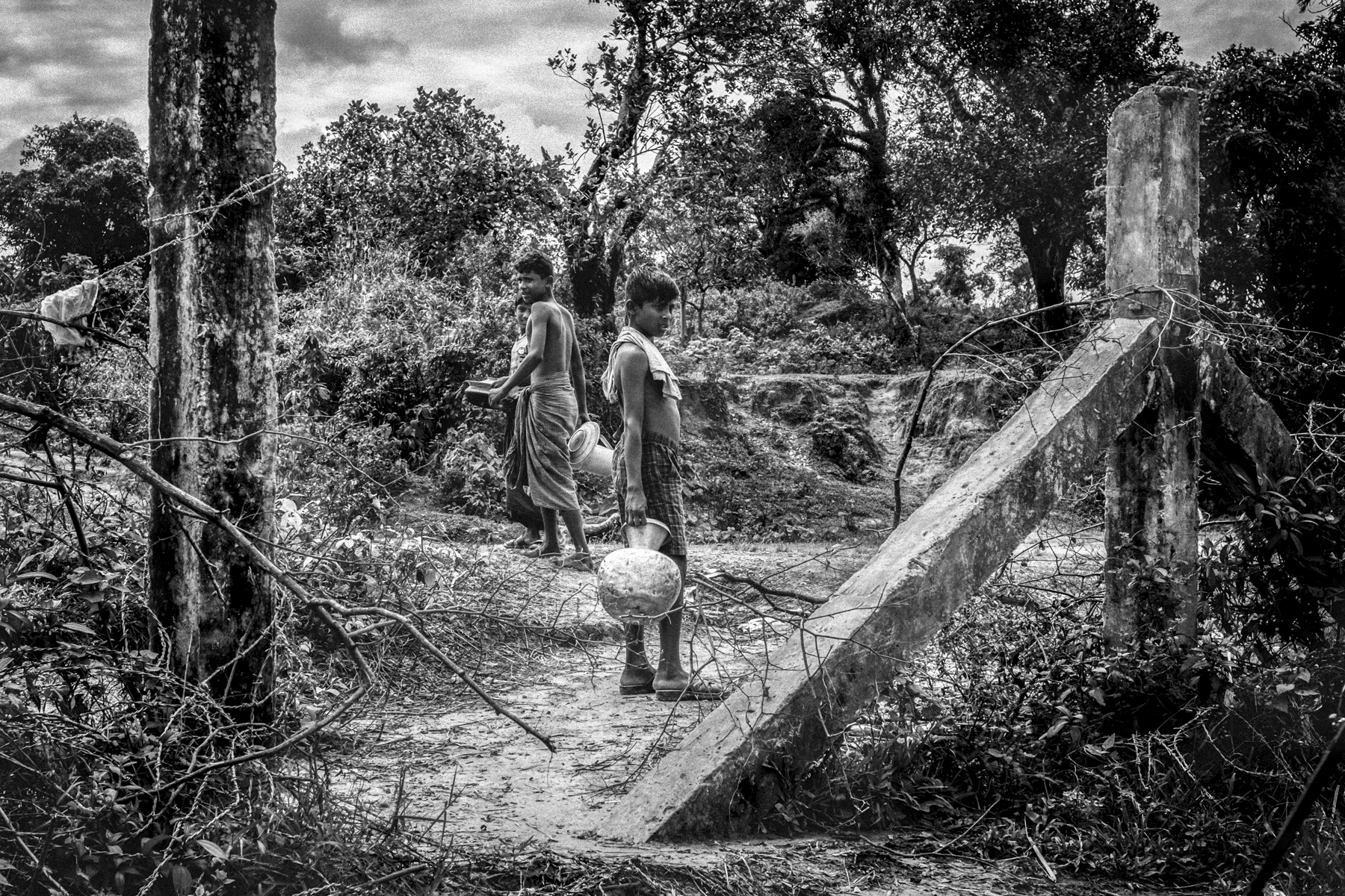 Rohingya boys walk through a hole in the border fence that separates Maungdaw, Myanmar from an area where they live in makeshift huts known as No Man's Land which lies between Myanmar and Bangladesh.