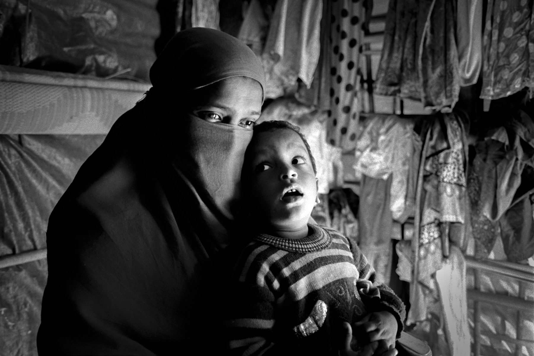 20 year old Fatema Begum holds her son Mehadi Hassan in a makeshift hut at Kutupalong refugee camp.  Her village Bagkunah in Maungdaw was attacked by Myanmar's military on September 5th, 2017.  Her 3 year old son and husband were killed in front of her.  She was then taken to a military outpost with around 20 other women were they were beaten and gang raped for a day.  Fatema was one of 8 of the women that managed to escape.