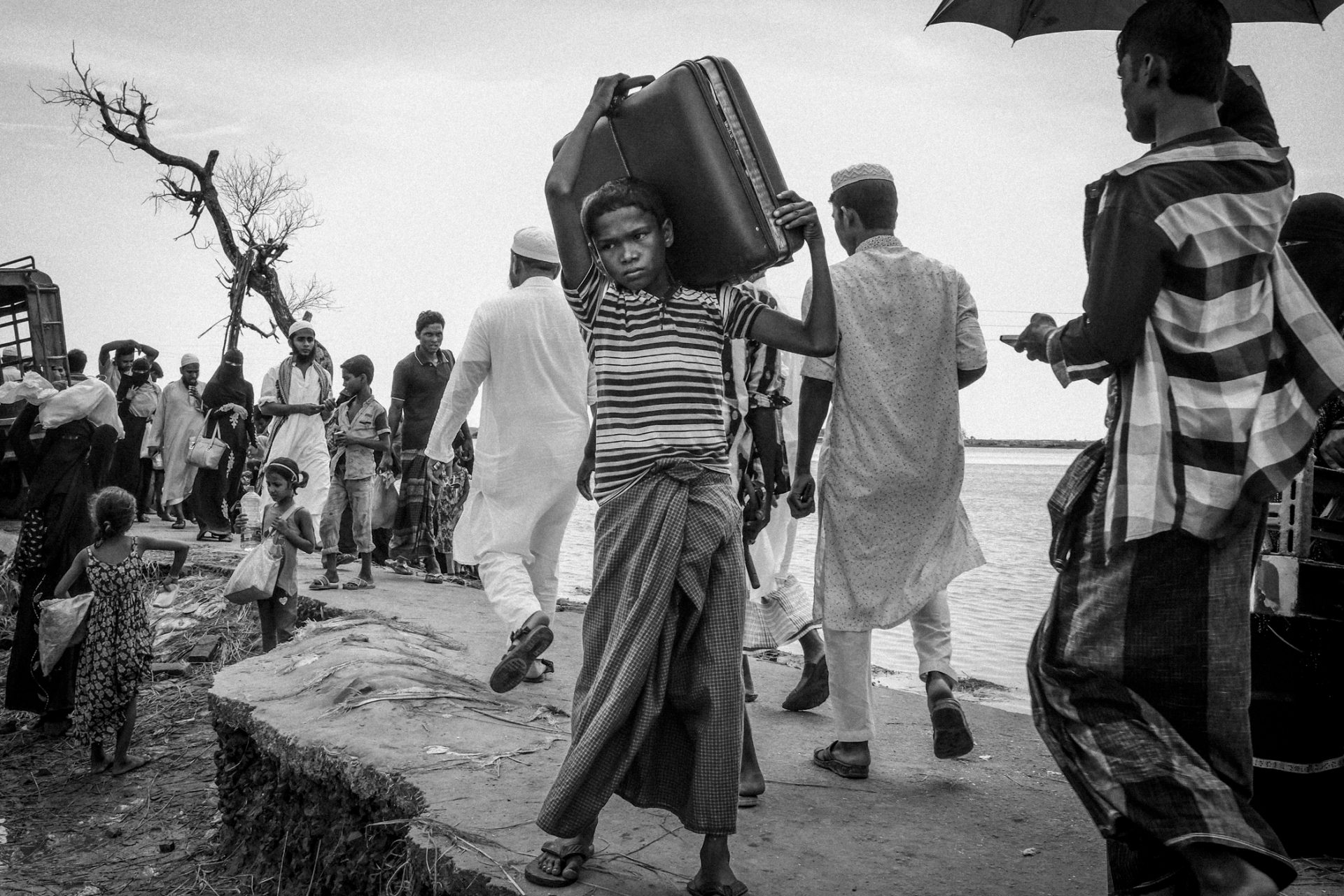 A Rohingya boy carries what belongings he could salvage as he enters Shah Porir Dwip, Bangladesh after fleeing Myanmar do to clearance operations carried out by the Myanmar military.