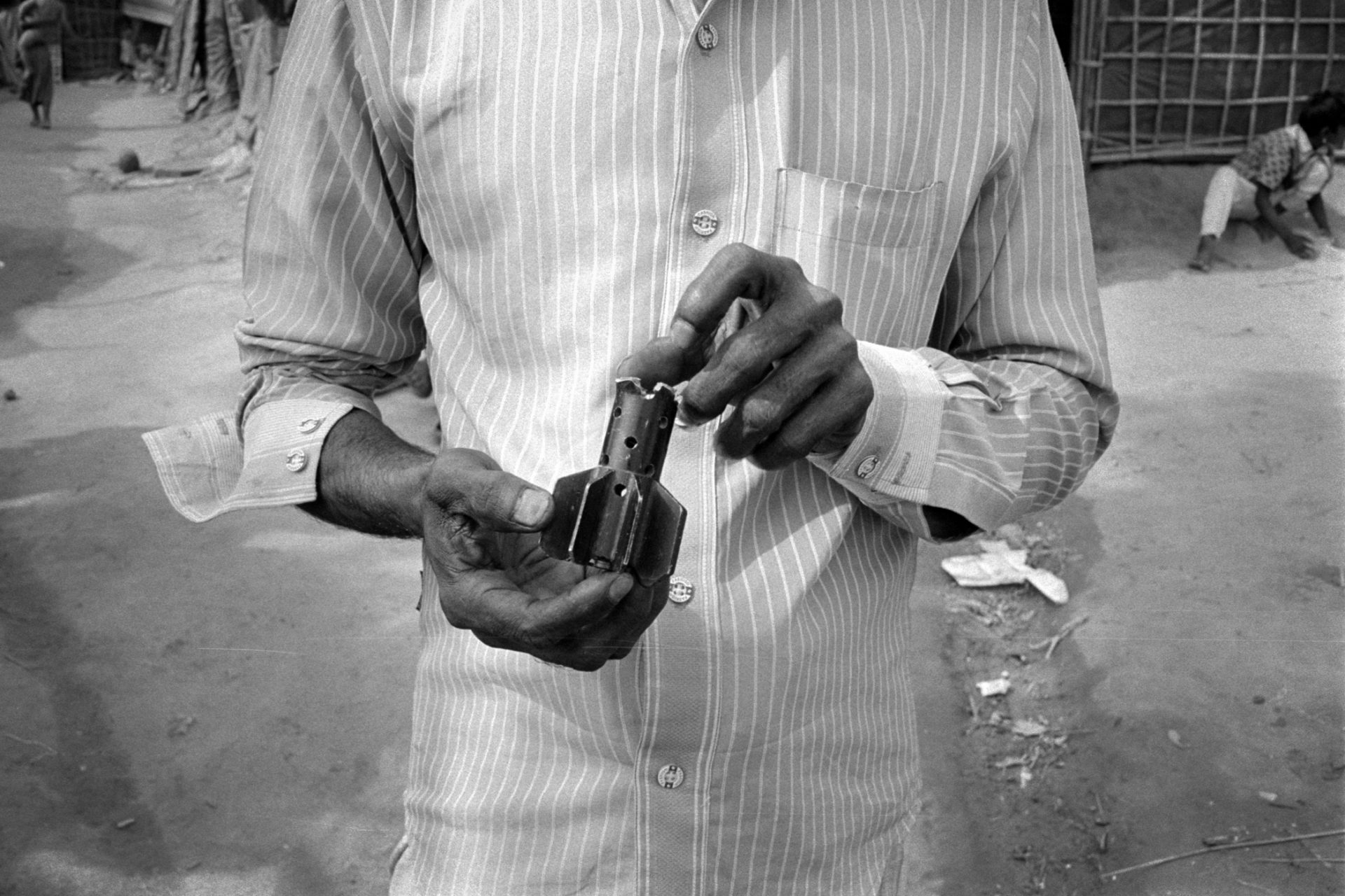 A Rohingya man holds a piece of shrapnel from a rocket propelled grenade used on by the Myanmar military when they attacked his village in Maungdaw, Rakhine State.
