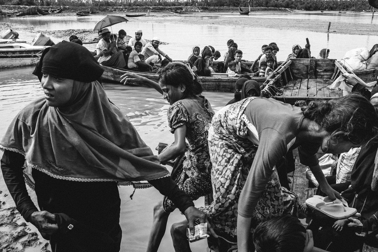 Newly arrived Rohingya refugees board boats at Shah Porir Dwip to be ferried to Bangladesh's mainland.
